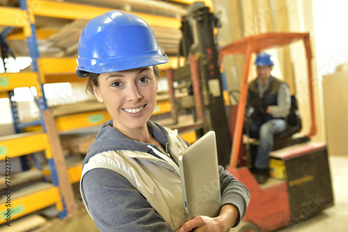 Smiling woman working in warehouse - 77522377