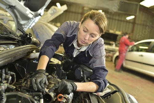 Technician woman working in auto repair workshop - 77522585