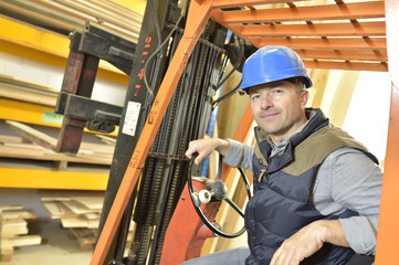 Operator in warehouse driving trolley
