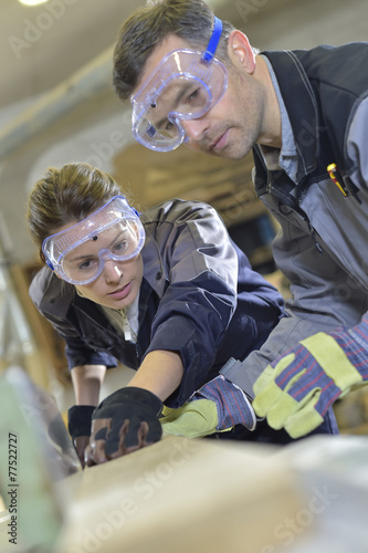 Instructor showing trainee how to use sawing machine - 77522727