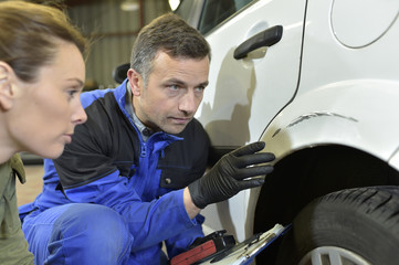 Mechanician with insurance adjuster checking on auto repair