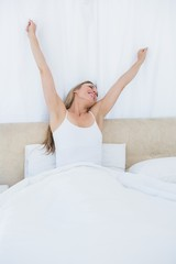 Happy blonde woman stretching in bed