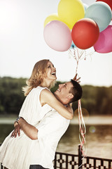 Young attractive happy couple with colorful ballons embracing an