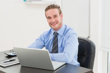 Cheerful stylish businessman using laptop