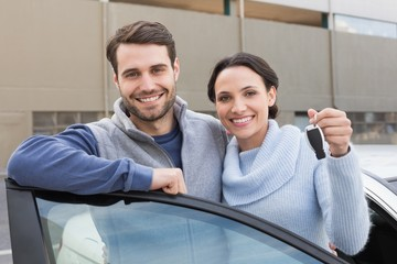 Young couple smiling holding new key