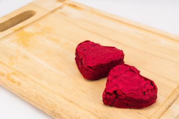 Heart shape Red Velvet cake on wooden plate