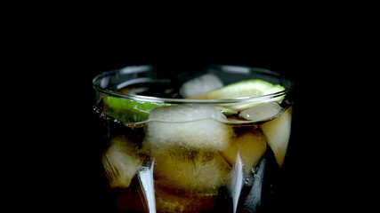 Pieces of lime fall into coke with ice cubes in slow motion