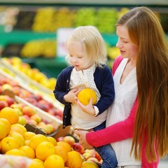 Mother and daughter choosing an orange in a store