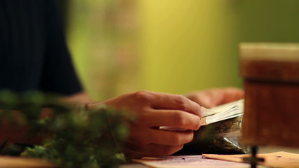 Close up of a man reading a book about herbs and hops