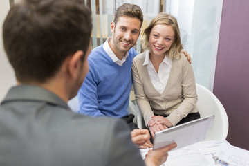 Couple meeting real-estate showing a investment project on pc