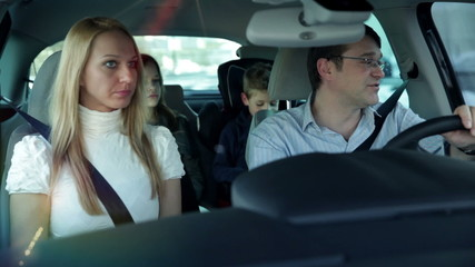 a young, beautiful family with two children who are having fun back in the car, while driving in a car to a certain destination