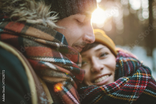 Young man hugs his girlfriend in winter forest - 77528772