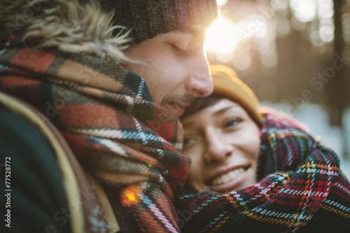 Leinwanddruck Bild Young man hugs his girlfriend in winter forest