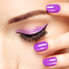 Woman's eye with violet  eye makeup and nails