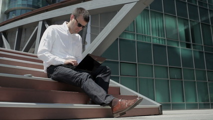 Businessman working on laptop outdoor