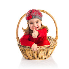 Cute baby inside basket with thumb up