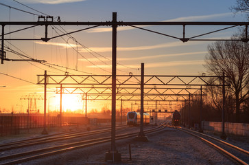 Railroad tracks at a station at a winter sunrise.