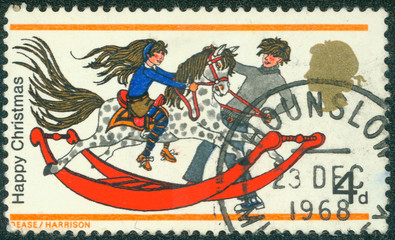 stamp shows boy and girl with rocking horse