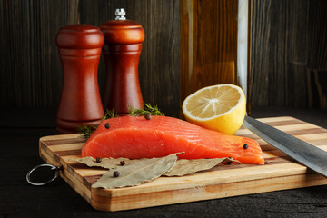 Piece of salmon with spices on cutting board closeup