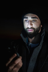 Young man uses his mobile at night