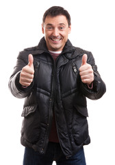 Handsome man in a down jacket showing his thumbs up
