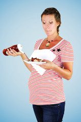 Hungry pregnant woman holding a ketchup bottle.