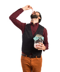 Man wearing waistcoat holding glass jar with sweets inside