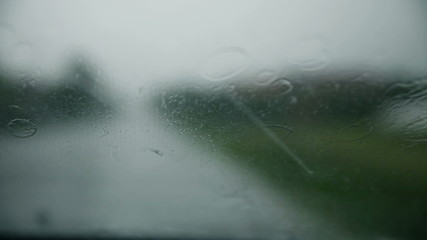 Rain drops falling on windshield while driving