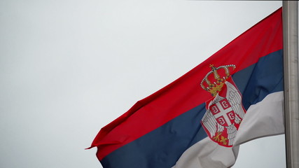 Serbian National Flag flapping in the strong wing, waving banner