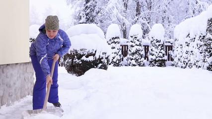 Young female shoveling near own house after snowfall