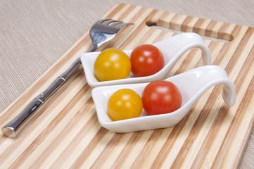 Tomate cherry con cubiertos.