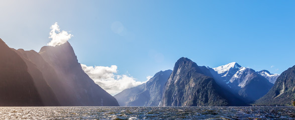 Majestic snow capped peaks of Milford Sound with sun rays. Fiord