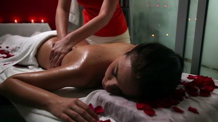 Young woman enjoying massage in a beauty spa salon
