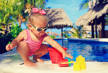 little girl playing in swimming pool at tropical beach