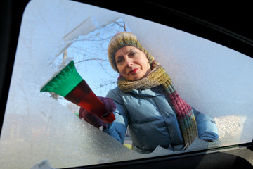 Automotive, woman cleaning ice from windshield with scraper
