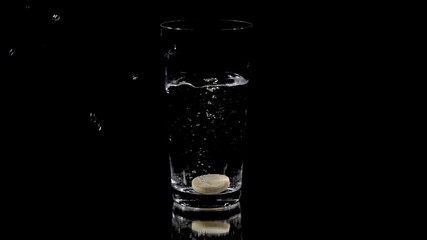 Vitamin tablet circling slightly at the bottom of the glass of water