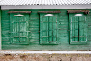 Three traditional russian wooden window in a wall painted in gre
