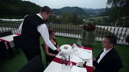 young couple is served with dinner by wait
