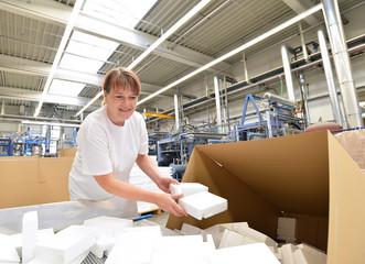 Frau verpackt Waren zum versenden in einer Fabrik