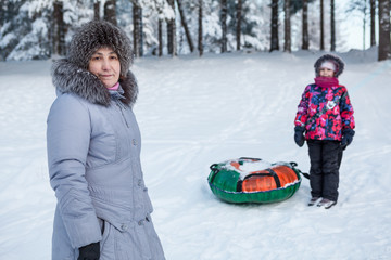 Mature mother portrait at winter with daughter with tube