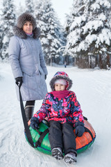 Senior mother and young child portrait with snow tubing