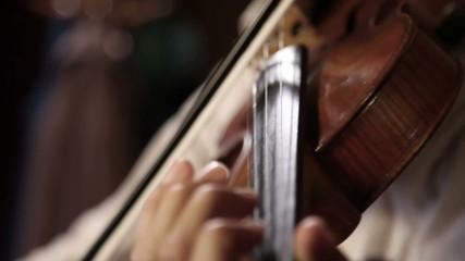 Close up pan shot of a violin player