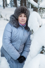 Caucasian woman looking at camera while stands in wintry forest