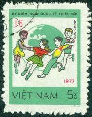 stamp printed in Vietnam shows Children dance around Globe