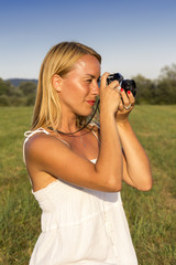 Pretty blonde woman with vintage photo camera