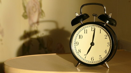 Vintage alarm clock on nightstand counts the time and then loudl