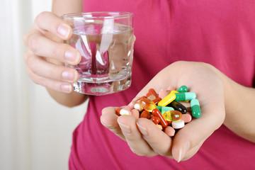 Frau mit Tabletten, Pillen und Kapseln als Medizin