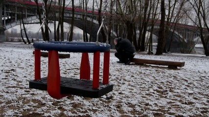 Empty swing and weeping father.