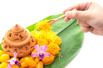 Thai dessert on banana leaf with hand