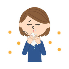 A young woman sneezing, allergen flowing in the air